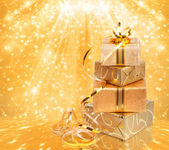 Gift box in gold wrapping paper on a beautiful abstract backgrou — Stockfoto