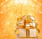 Gift box in gold wrapping paper on a beautiful abstract backgrou — Stock Photo
