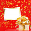 Gift box in gold wrapping paper on a beautiful red abstract back — Stock Photo