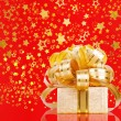 Stock Photo: Gift box in gold wrapping paper on beautiful red abstract back