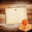 Old sheet of paper with gift box on grunge wooden background — Stock Photo