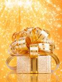 Caja de regalo en papel de envolver en un hermoso backgrou abstracto de oro — Foto de Stock