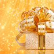 Gift box in gold wrapping paper — Stock Photo