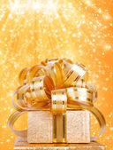 Gift box in gold wrapping paper on a beautiful abstract background — Stock Photo