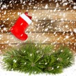 Snowy pine branch with Red christmas boot on the old wooden wall — Stock Photo