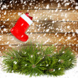 Snowy pine branch with Red christmas boot on the old wooden wall — Stock Photo #34899165