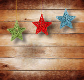 Christmas multicoloured stars on old wooden background — Stock Photo