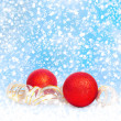 Red Christmas balls with golden streamer on a snowy blue backgro — Стоковая фотография