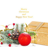 Christmas tree branch with gold serpentine, gift box and red sph — Stock Photo