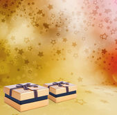 Beautiful Gift gold box with bow on the abstract star background — Stock Photo