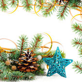 Christmas tree branch with gold serpentine and star on white bac — Photo