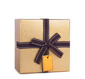 Beautiful gift box in gold paper with bow and label — Stock Photo