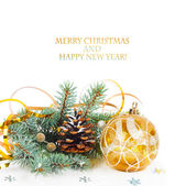 Christmas tree branch with gold serpentine and yellow sphere — Stock Photo
