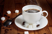 Hot fresh coffee in a white cup with sugar — Stock Photo