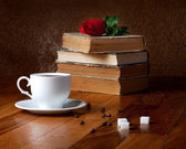 Hot cup of fresh coffee and stack of books — Stock Photo
