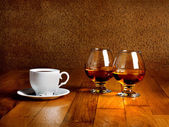 Two goblets of brandy and cup of hot coffeeon wooden old counter — Stock Photo