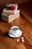 Hot cup of fresh coffee on the wooden table and stack of books t — 图库照片