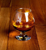 One glass of brandy on antique wooden counter top  — Stock Photo