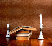 Old stack of books with candlestick and burning candle on the wo — Stock Photo