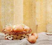 Fresh chicken eggs in straw nest on wooden wall background — Stock Photo