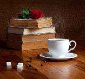 Hot cup of fresh coffee and books — Stock Photo