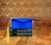 Graduation mortarboard on top of stack of books on a wooden tabl — Stock Photo