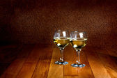 Two wineglasses of white wine on wooden old counter top — Stock Photo