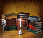 Books with candlestick and burning candle — Stock Photo