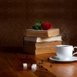 Hot cup of fresh coffee on the wooden table and stack of books t — Stock Photo #43606387