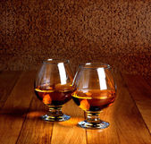 Two goblets of brandy on wooden old counter top  — Stock Photo