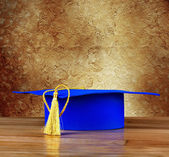 Graduation mortarboard on wooden table on background of vintage  — Stockfoto