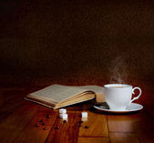 Hot cup of fresh coffee on the wooden table and a stack of books — Foto de Stock