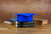 Graduation mortarboard on top of stack of books on abstract back — Stock Photo