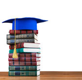 Graduation mortarboard on top of stack of books — Stock Photo