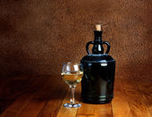 Dusty old bottle and glass of white wine on a wooden table — 图库照片