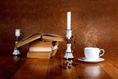 Taza de café recién hecho en la mesa de madera con vela y libro — Foto de Stock