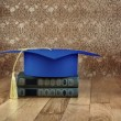 Graduation mortarboard on books — Stock Photo