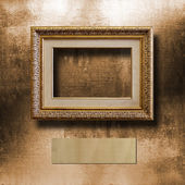 Old gilded picture frame for  portrait on  shabby cement wall — Stok fotoğraf