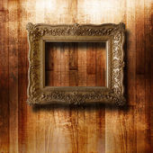 Old gilded picture frame for portrait on the scratched wooden wa — Stok fotoğraf