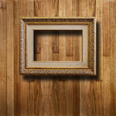 Old gilded picture frame for portrait on the scratched wooden wa — Stock Photo