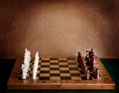 Wooden chess board with figures on green table and old wall — Stock Photo