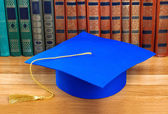 Graduation mortarboard on top of stack of books — 图库照片