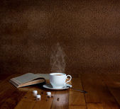 Hot cup of fresh coffee on the wooden table and a stack of books — Stock Photo