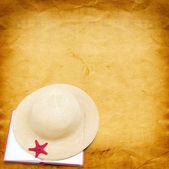 Straw hat with book and red starfish on shabby paper background — Stockfoto