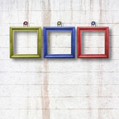 Multicolored wooden frames on old stone wall — Stock Photo