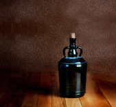Old dusty bottle on a wooden table vintage — Stock Photo