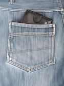 Black leather wallet sticking in the back pocket of denim  blue — Stock Photo