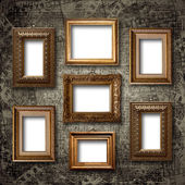 Gilded wooden frames for pictures on old stone wall — Stock Photo