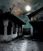 Halloween pumpkins in the yard of an old house at night in the b — Stock Photo