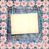 Old vintage postcard with beautiful pink flowers on blue jeans b — Stock Photo